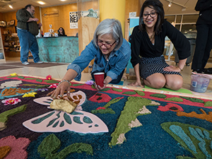 Participants in a previous Big Read community event create alfombras de aserrín, a sawdust carpet traditionally made during Holy Week to celebrate Easter in Guatemala