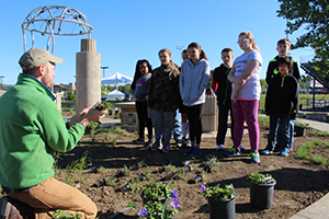 Portsmouth City School District students stand in a flower bed in the Human Rights Garden, a plant and sculpture garden created by Portsmouth students and teaching artists as part of an Ohio Arts Council TeachArtsOhio grant