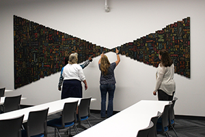 "Kent State University faculty members search for the title hidden in Shane Allbritton's piece, ""Thinking Made Visible."" Allbritton was commissioned to create two pieces relating to communications for KSU's newly renovated Taylor Hall"