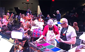 A screenshot of a dress rehearsal at the Fitton Center for the Creative Arts. Image shows an orchestra seated on stage next to a live printmaking session.