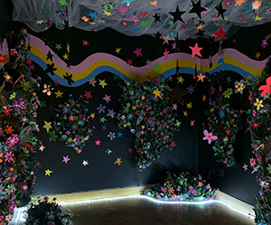 Black painted room, lit with blue LED lights, filled with brightly colored, sparkly flowers.