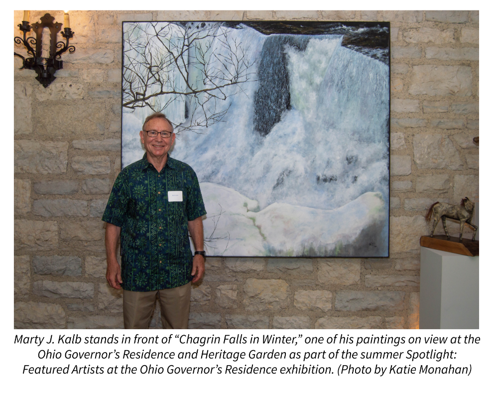 "Marty J. Kalb stands in front of ""Chagrin Falls in Winter,"" one of his paintings on view at the Ohio Governor's Residence and Heritage Garden as part of the summer Spotlight: Featured Artists at the Ohio Governor's Residence exhibition. Photo by Katie Monahan."