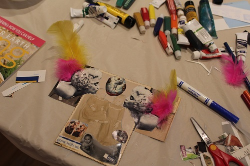 """""""Deface This"""" workshop materials, including feathers, photos, markers, and glue, on a table"""