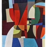 A multicolored quilt arranged in a modern Cubist pattern