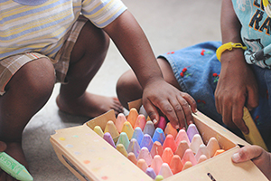 Two children kneel next to a box of crayon-shaped sidewalk chalk