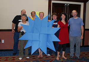 A group photo of people posing with a large blue folded giant origami piece